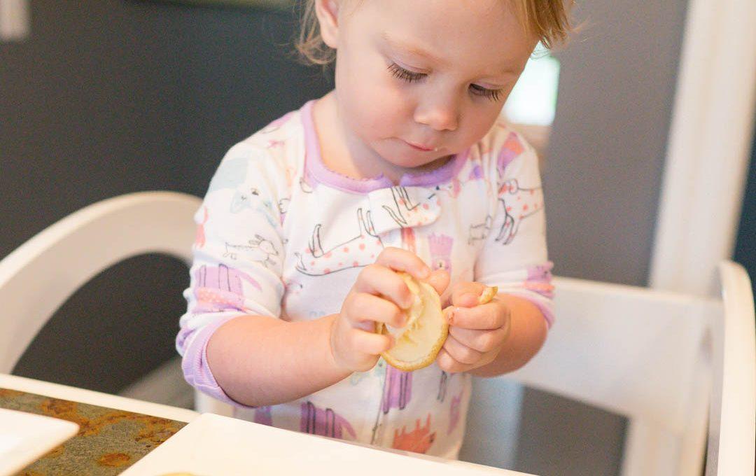 toddler slicing fruit